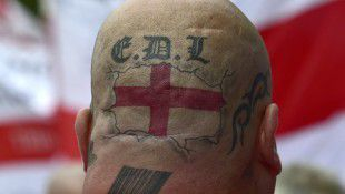Tattoos are seen on the back of the head of a supporter of the English Defence League during a rally outside Downing Street in London