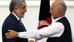 Afghan rival presidential candidates Abdullah and Ghani shake hands after exchanging signed agreements for the country's unity government in Kabul