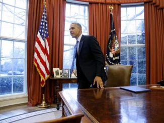 President Barack Obama gets up from his desk after signing the memorandum