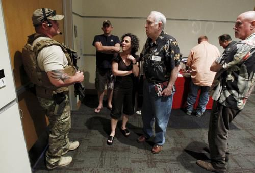 A police officer prevents attendees from leaving the Muhammad Art Exhibit and Contest after shots were fired outside the venue in Garland, Texas May 3, 2015.