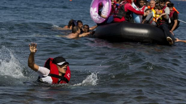 A Syrian man swims in front of a dinghy full of refugees. Photo: Petros Giannakouris