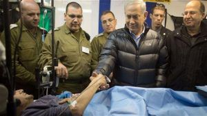 Israeli Prime Minister Benjamin Netanyahu shaking hands with a militant in an Israeli field hospital in Syria's occupied Golan Heights.