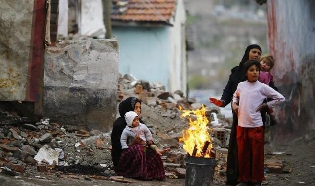 Syrian refugees warm themselves around a fire in Hacibayram district of Ankara