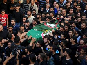 Mourners carry the coffin of the Shia Amal Movement party's Hussein Hojeij, who died in the blast