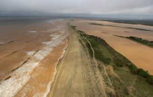 A general view the sea (L) and  Rio Doce (Doce River), which was flooded with mud after a dam owned by Vale SA and BHP Billiton Ltd burst, as the river joins the sea on the coast of Espirito Santo in Povoacao Village, Brazil, November 22, 2015. REUTERS/Ricardo Moraes - RTX1VA3G