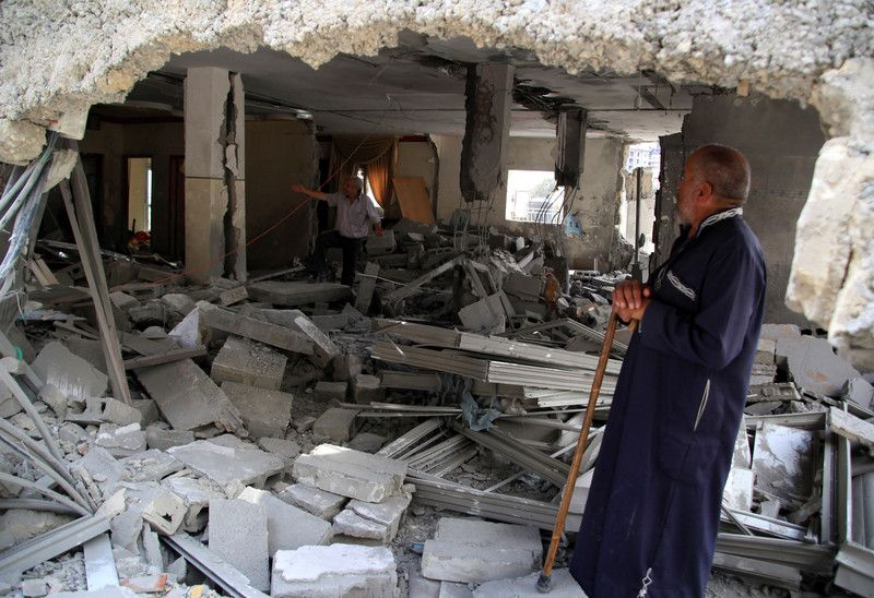 An old Palestinian man surveys his house after it got punitively demolished