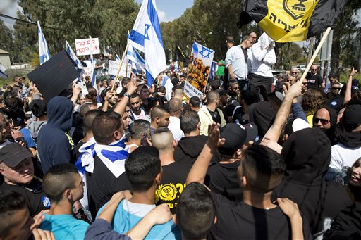 Israeli right wing protesters wave flags outside of Castina military court