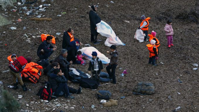 Migrants wearing life jackets wait for a dinghy to sail off for the Greek island of Lesbos from the Turkish coastal town of Dikili
