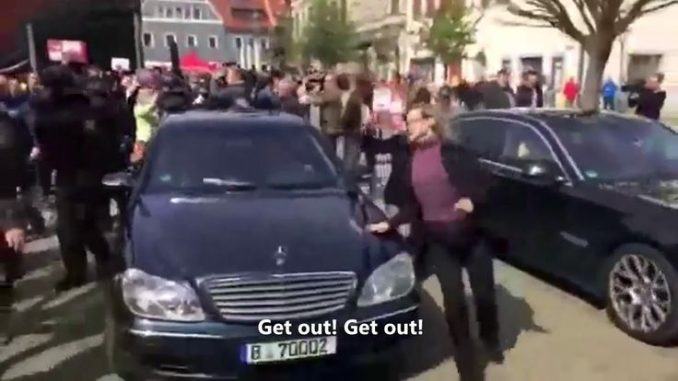 """German minister flees crowd after they shout """"traitor"""""""