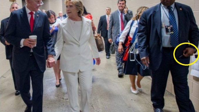 Evidence has emerged that Hillary's handler - a man who carries what looks like a medical lapel-pin - always has an auto-injector syringe with Diazepam on hand.