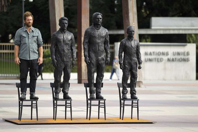 """Italian artist Davide Dormino stands on an empty chair in his installation """"Anything to Say?"""""""
