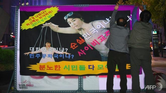 Posters of the president being controlled by puppet strings are cropping up all over South Korea as country-wide protests continue to rage.