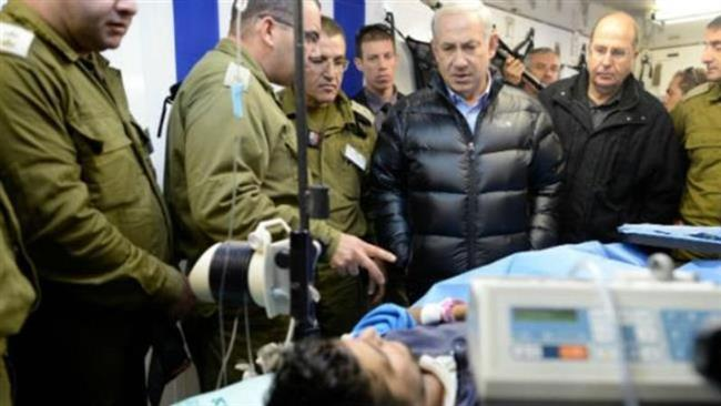 Israeli Prime Minister Benjamin Netanyahu, third right, visits a militant wounded in Syria at a field hospital in northern Israel, February 2014.