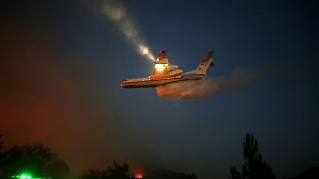 An Israeli firefighter plane helps extinguish a fire in Haifa on November 24, 2016. (Photo by AFP)