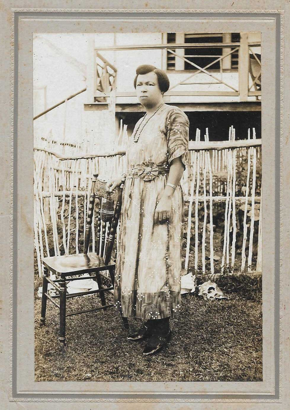 Miss Chrishy dressed up in her usual finery, standing in front of the home at Orange Hill, St Ann parish where I spent my early years