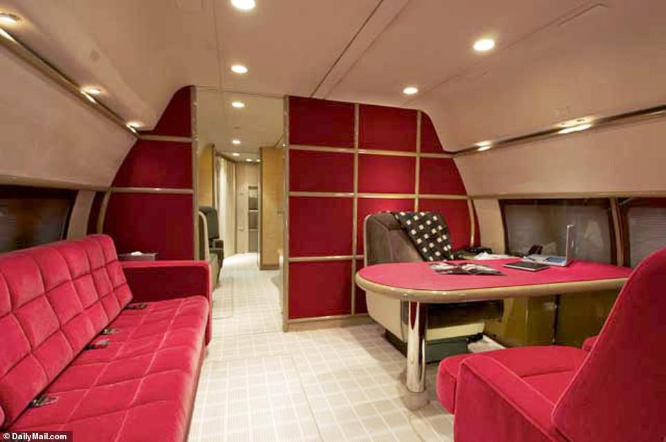 In one room that looks like an office, an Apple laptop computer and Apple iPad sit on the desk and the room has a red velvet chairs and a sofa