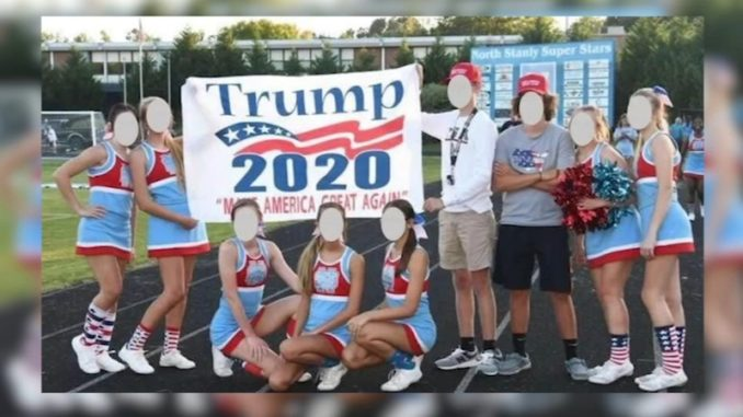 High school cheerleaders at a North Carolina school have been put on probation after posing with a Trump 2020 banner.