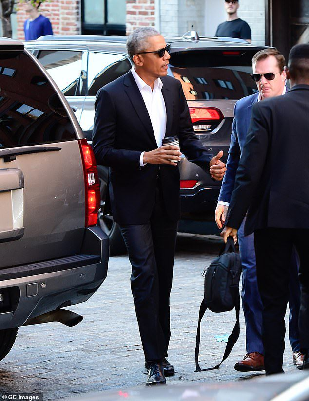 The former US president was caught in Manhattan wearing a black suit and sunglasses while holding a takeaway coffee on his way to meet Robert De Niro