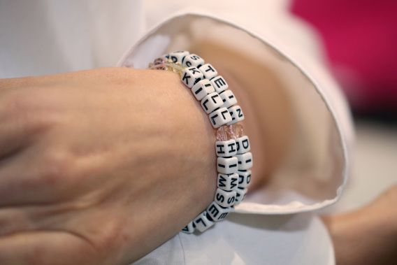 One of Epstein's victims, identified only as Jane Doe 15, wore an 'EPSTEIN DIDN'T KILL HIMSELF' bracelet during press conference Monday.