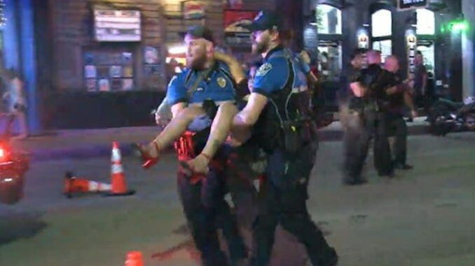 One of two suspects has been arrested over a mass shooting in downtown Austin that left 14 people injured during a night out in the Austin's entertainment district.